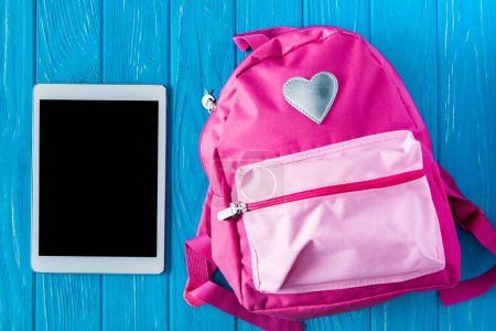 top view of digital tablet with blank screen and pink backpack on blue wooden background