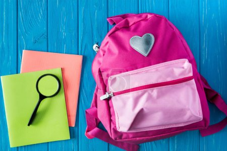 top view of textbooks, magnifier and pink backpack on blue wooden background
