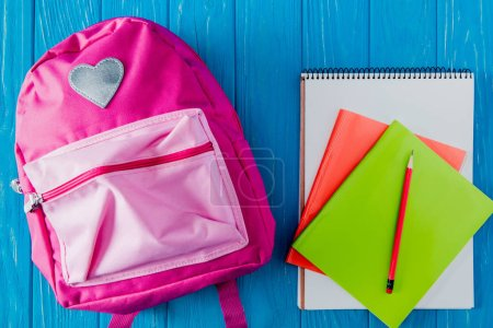 top view of pink backpack, blank notebook, textbook and pencil on blue wooden background