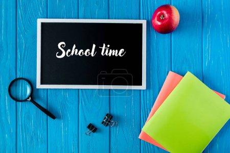 Photo pour Vue de dessus du tableau noir avec lettrage temps scolaire, pomme et papeterie sur fond de bois bleu - image libre de droit