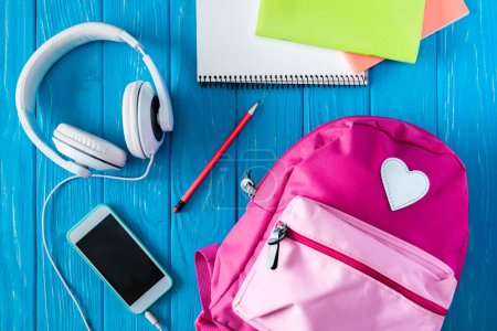 top view of pink rucksack, smartphone with blank screen, headphones and textbooks on blue wooden background