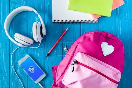 Foto de Vista superior de los auriculares, mochila rosa, smartphone con la aplicación shazam y papelería sobre fondo de madera azul - Imagen libre de derechos