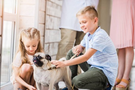 Photo for Children palming pug dog at animals shelter - Royalty Free Image
