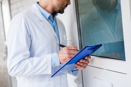 cropped image of veterinarian with clipboard checking rooms at veterinary clinic