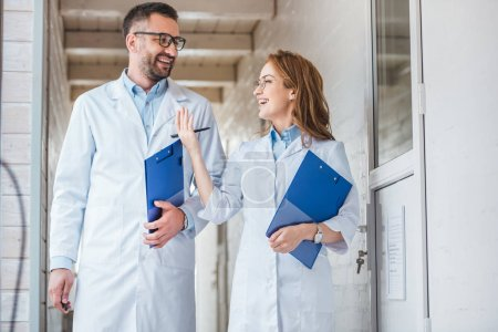smiling vets in white coats walking with clipboards in veterinary clinic and looking at each other
