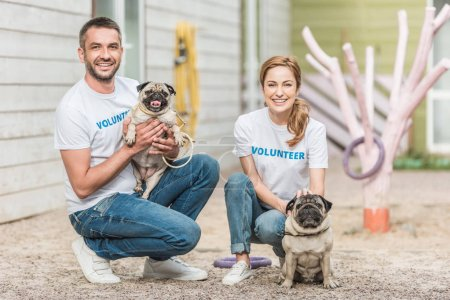 two volunteers of animals shelter squatting with pug dogs and looking at camera