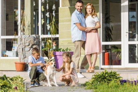 Photo pour Parents heureux en regardant les enfants jouer avec le chien à l'extérieur de la maison - image libre de droit