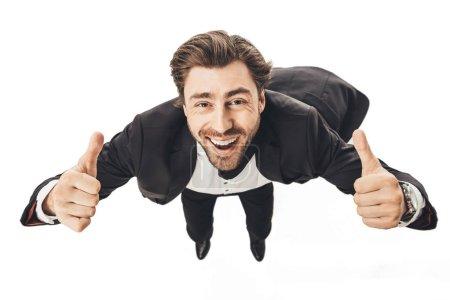 Foto de Primer disparo del hombre de negocios joven sonriente cayendo y que muestran los pulgares arriba aisladas en blanco - Imagen libre de derechos