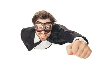 handsome young businessman in vintage aviation goggles flying like superhero isolated on white