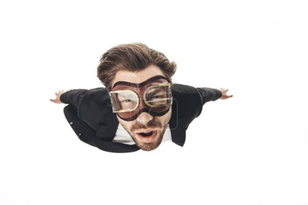 handsome young businessman in vintage aviation goggles falling isolated on white