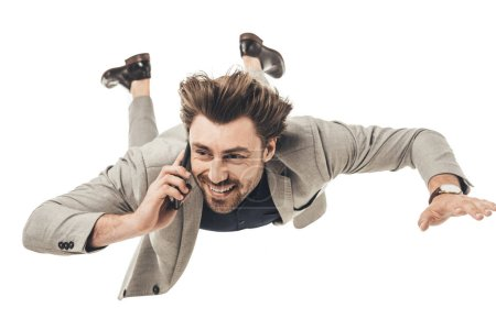 happy young businessman talking by phone while falling isolated on white