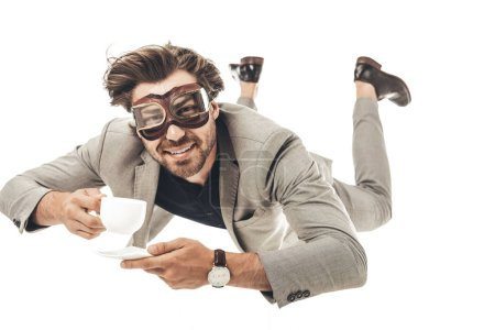 handsome young businessman in vintage aviation goggles falling with cup of coffee isolated on white