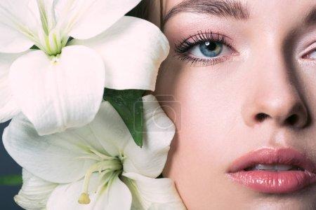retrato de vista parcial de hermosa mujer joven con flores de lirio blanco