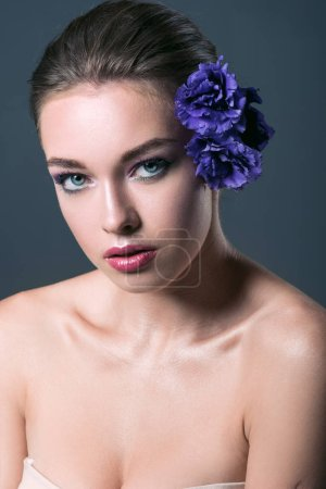 attractive young woman with eustoma flowers in hair looking at camera isolated on grey