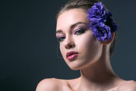 Photo pour Portrait de gros plan de la séduisante jeune femme avec des fleurs d'eustoma derrière l'oreille en regardant la caméra isolée sur fond gris - image libre de droit