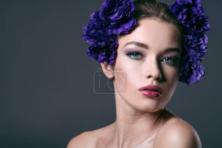 close-up portrait of beautiful young woman with eustoma flowers on head looking at camera isolated on grey