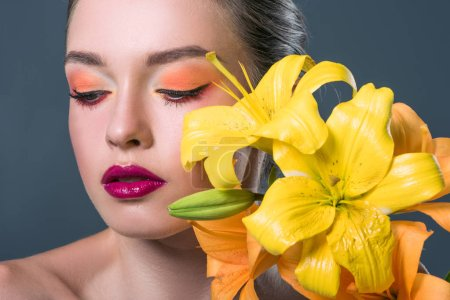 close-up portrait of beautiful young woman with fashionable makeup and yellow lilium flowers  isolated on grey