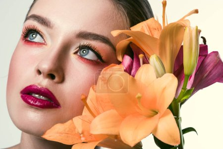 close-up portrait of beautiful young woman with stylish makeup and orange lilium flowers looking up isolated on white