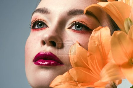 close-up portrait of beautiful young woman with stylish makeup and orange lilium flowers isolated on grey