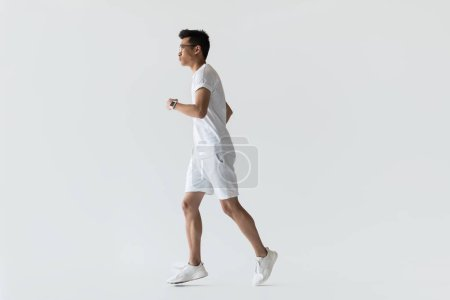 side view of young asian sportsman running on grey background