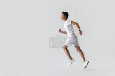 side view of young asian male athlete running on grey background