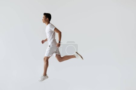 Photo for Side view of young asian jogger running on grey background - Royalty Free Image