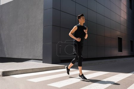 handsome young asian sportsman running at urban street