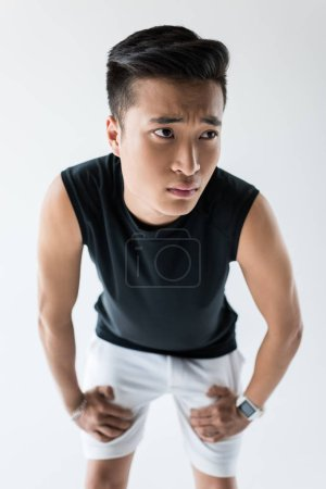 selective focus of serious asian sportsman standing on grey background