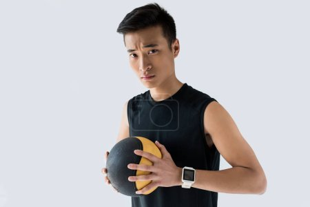 serious asian sportsman with smartwatch holding medicine ball isolated on grey background