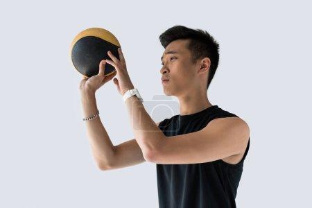 Photo pour Vue latérale du jeune sportif asiatique avec médecine-ball isolé sur fond gris - image libre de droit
