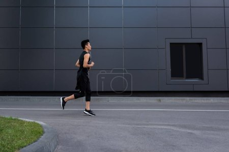 side view of young asian sportsman in earphones running at city street