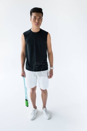 serious young asian sportsman standing with jump rope on grey background