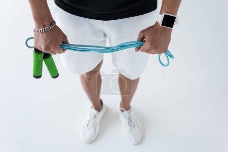 Photo pour Cropped image de jeune athlète masculin avec smartwatch tenant la corde à sauter sur fond gris - image libre de droit