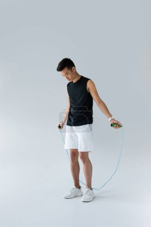 Photo for Young asian male athlete exercising with jump rope on grey background - Royalty Free Image