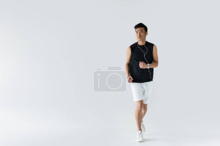 serious young asian sportsman in earphones running on grey background