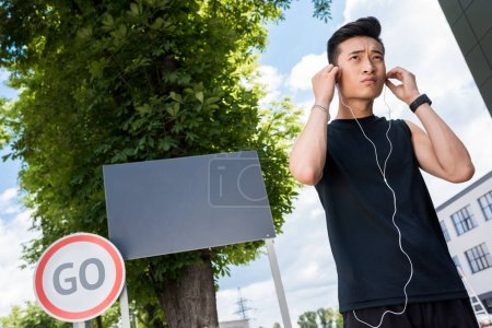 low angle view of serious asian sportsman putting on earphones at street with empty signboard and road sign with lettering go