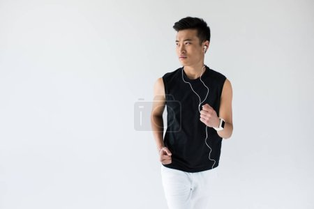 serious young asian male athlete in earphones running on grey background