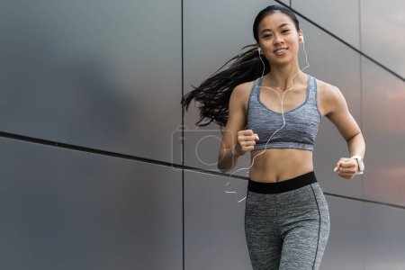 smiling young asian sportswoman in earphones running at city street