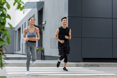 smiling asian sportsman and sportswoman running at city street