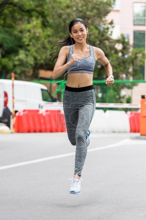 smiling young asian female jogger running in earphones running at city street