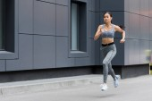attractive young asian sportswoman in earphones running at city street