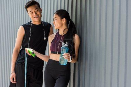 Photo pour Souriant bouteille tenue sportive asiatique de l'eau et donnant la corde à sauter au jeune sportif à la rue - image libre de droit