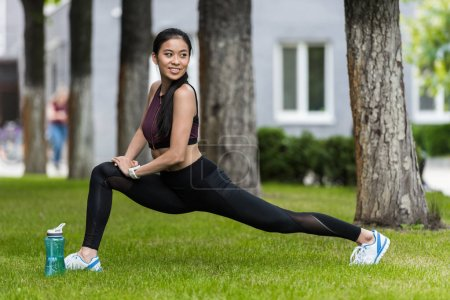 smiling asian female athlete stretching near sport bottle of water on grass in park