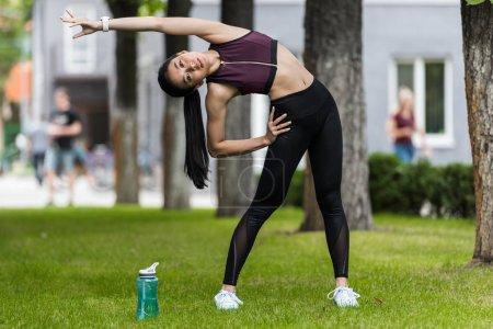 asian female sportswoman stretching near sport bottle of water on grass in park