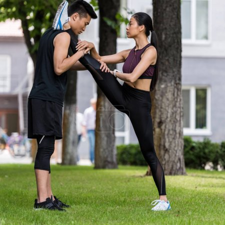 young asian sportsman helping female athlete to stretch on grass in park