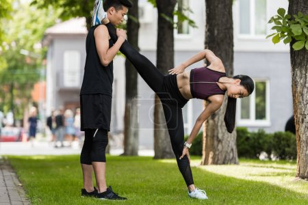 asian sportsman helping female athlete to stretch on grass in park
