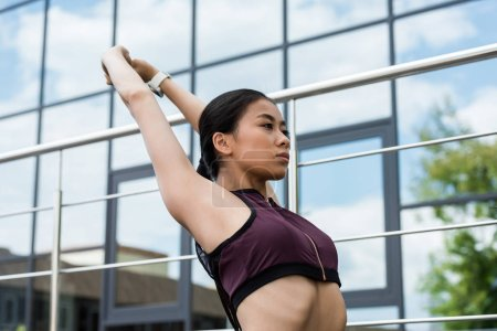 Photo for Young asian sportswoman stretching at city street - Royalty Free Image