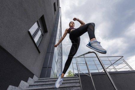 Photo pour Vue à angle bas de la sportive asiatique sautant des escaliers à la rue urbaine - image libre de droit