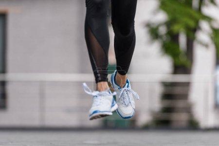 cropped image of female athlete running at urban street