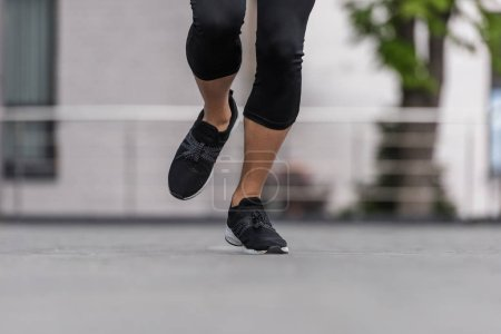 cropped image of female athlete in sneakers running at street